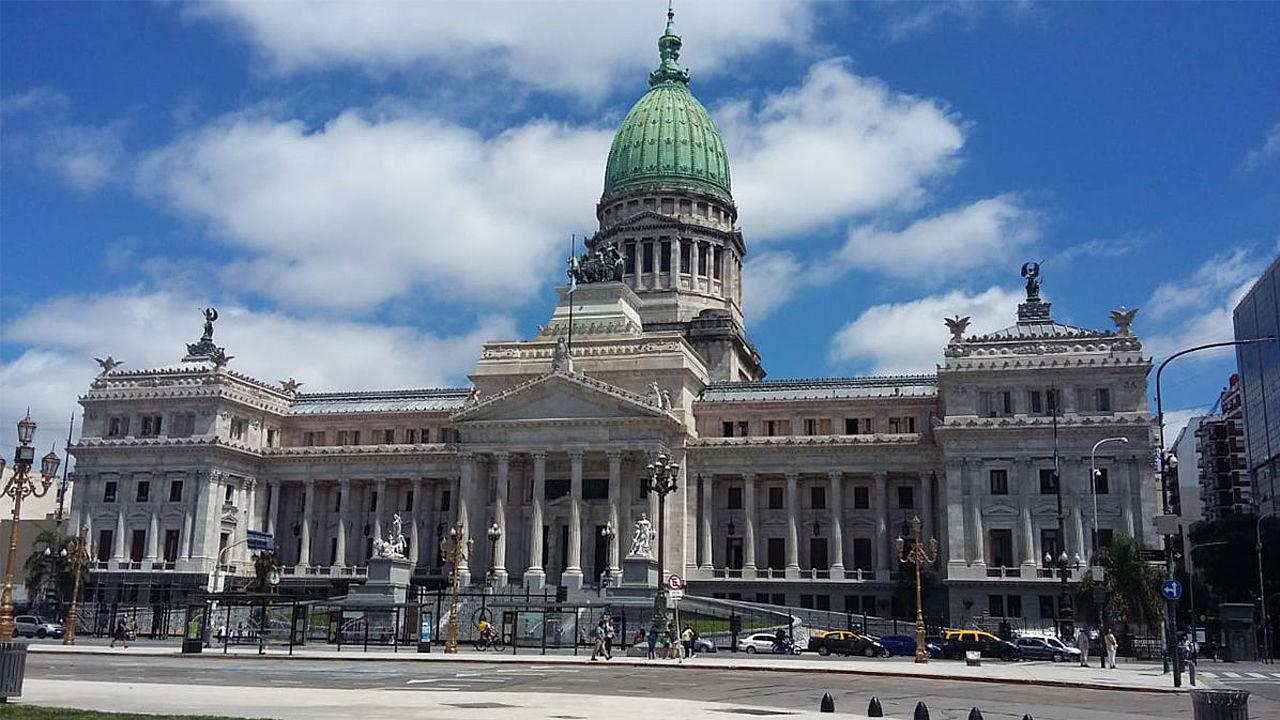Congreso de la Nación un dia soleado con algunos autos y peatones pasando delante