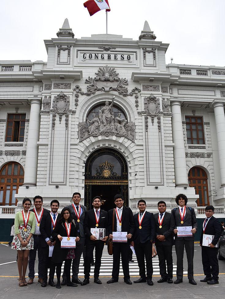 Parlamentarios jóvenes en las afueras del Congreso muestran sus certificados de participación.